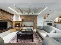 Salon z cegłą na ścianie i eklektycznymi meblami. Aranżacja salonu z kominkiem